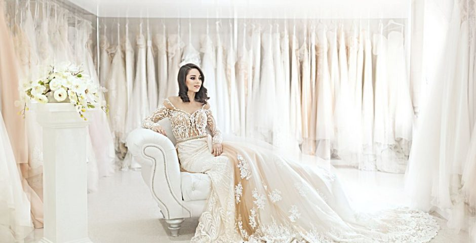 Bride sitting on chaise in a bridal parlour wearing a long-sleeved bridal gown