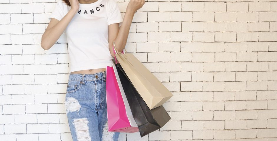 Woman against a brick wall holding many shopping bags